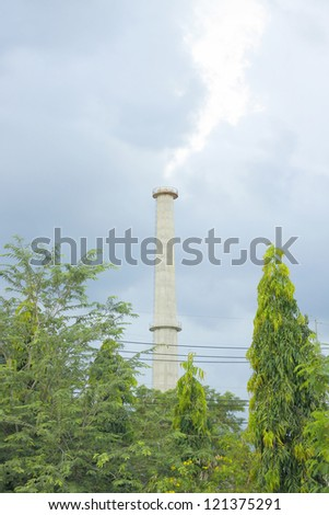 White Smoke out of Industrial Smokestack with grey clouds.