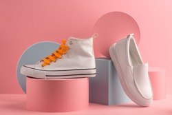 White sneaker and loafer on pink background with paper 3D shapes. Creative footwear concept for special offer design.