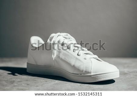 White sneaker on gray background. Stylish white sneaker