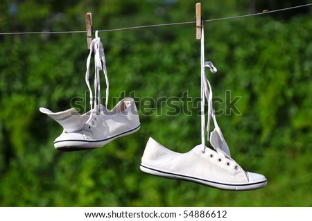 White sneakers are hanging on a clothesline