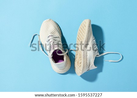 White sneakers on a blue background under the natural light of the morning sun. Concept of jogging, running, hard workout. Flat lay, top view