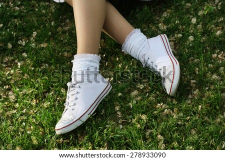 white sneakers on girl legs on grass during sunny summer day. #278933090