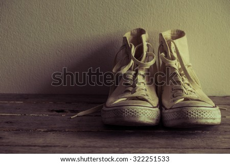 white sneakers on wooden in vintage look . youth culture and style.