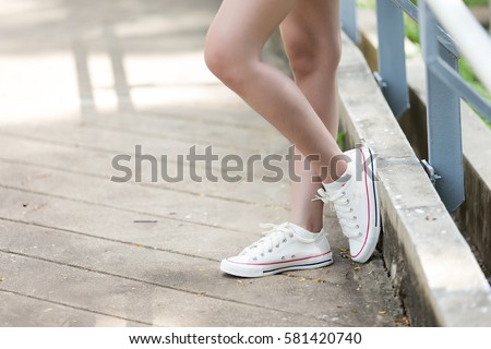 White sneakers women standing relax after exercising in the park in the morning. #581420740