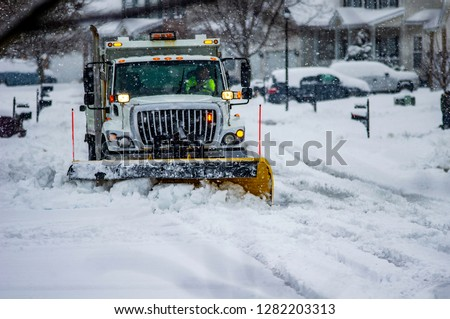 White snowplow truck with warning lights and yellow blade moving snow off of city streets while flakes are still falling