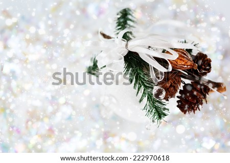 White snowy Christmas decoration with baubles, fir branch, and cones. Holiday greeting card concept.