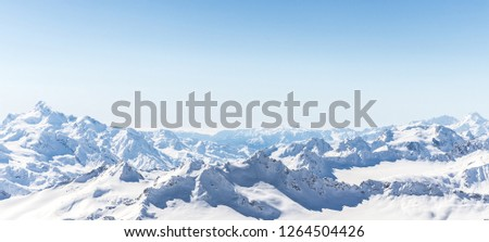 White snowy winter Caucasus mountains at sunny day. Panorama view from ski slope Elbrus, Russia #1264504426