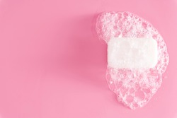 White soap bar and foam on pastel pink background. Flat lay, top view, copy space