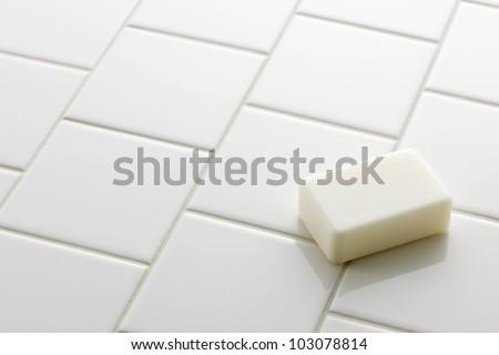 White soap bar on white tile floor