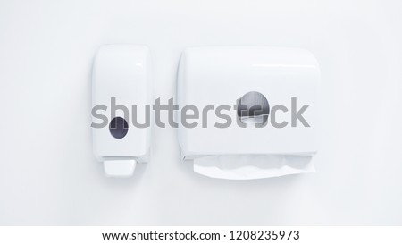 White soap dispenser pump and toilet paper towel dispenser on wall in bathroom