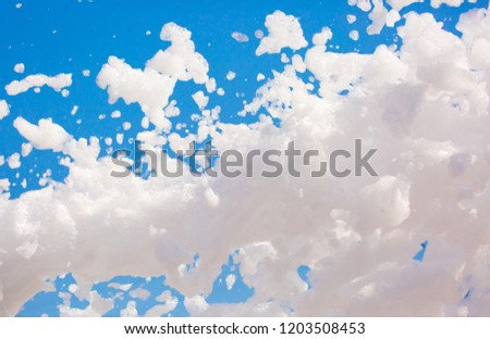 White soap foam on a blue sky background. Fun foam, background or texture of a white foam with copy space Entertainment foamy parties a summer entertainment festival in the water park