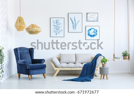 White sofa and blue armchair in living room with posters on the wall #671972677