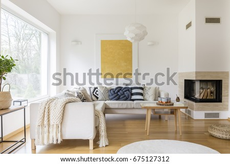 Shutterstock White sofa with pillows and modern fireplace in stylish living room
