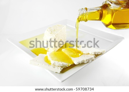 white soft cheese with olive oil on white dish