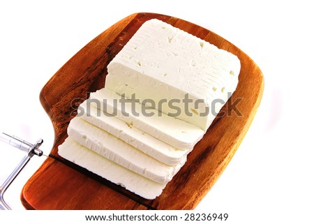 white soft goat cheese on cutboard over white