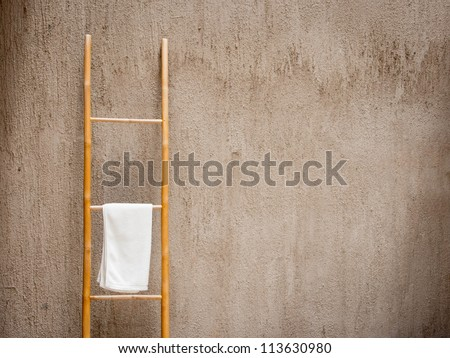 White spa towel hanging on bamboo stand