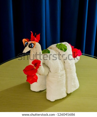 White spa towel twisted ( has been folded out of a towel )  in the form of an abstract animal, dinosaur. Decorated with flowers.