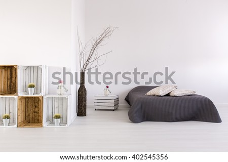 White, spacious bedroom with large bed, handmade nightstand and regale