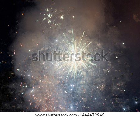 White sparkler burst with smoke, flying sparks, and light trails.  #1444472945