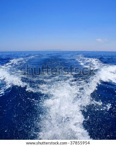 white speedboat wake on blue sea