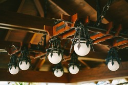 White spherical lamps. Antique black wrought iron chandelier under the wooden ceiling.