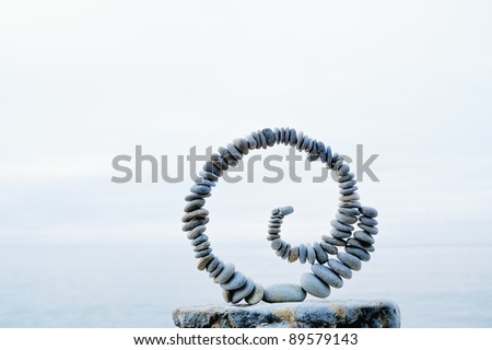 White spiral of pebbles on the boulder at the sea