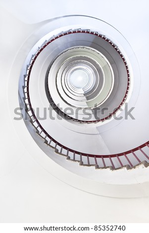 White spiral staircase with a red fence. - stock photo