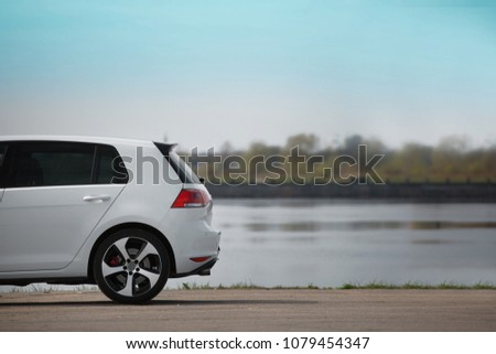 White sport hatchback parked on road side with river background