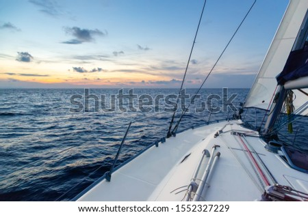 White sport sailing yacht goes under all sails in strong wind. Luxury yacht cruise on Andaman Sea of Indian Ocean. Sails raised, mast bent under the wind, waves, spray. Pleasure of tropical vacation