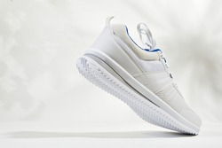 White sports sneakers with shoelace on white wall background. Man sneakers for fitness. White sneaker with leather accents.