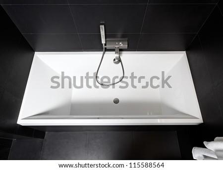 White square bathtub in modern black and white bathroom interior