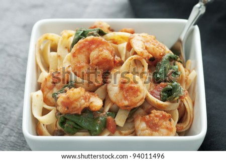 White square bowl of pasta with shrimp, tomato sauce and spinach
