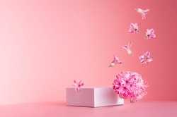 White square podium for display cosmetic and goods with hovering flow of fresh spring flowers  on gentle pastel pink background, copy space, modern fashion style.
