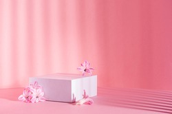 White square podium for presentation cosmetic, accessories and produce on sunny bright pastel pink background with striped shadows, spring hyacinth flowers, copy space.