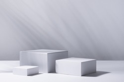 White square podiums in sunlight with shadow palm leaf in white space. Tropical showcase for cosmetic products, goods, shoes, bags, watches.