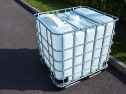 White square water tank. Water tank with metal grate. White huge container for liquid. Large water tank is outside. Сoncept is use of a container for liquid. Liquid reservoir reinforced a metal grid