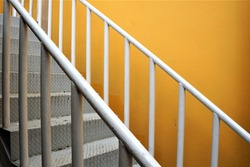 White stairs and banister outside the building near the yellow wall.The metal on the floor of the stair has a rough pattern to prevent slipping.