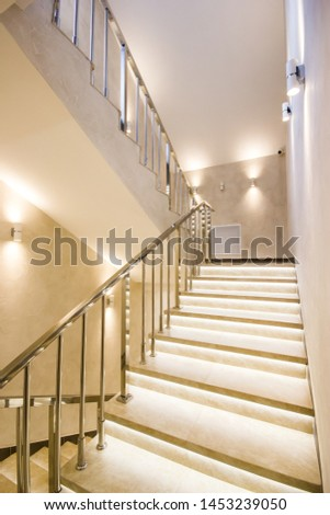 White stairs of modern building with illumination and with a handrail