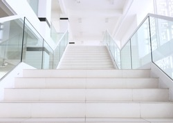 White stairs with steel and glass railing in a new modern building. white stairs going up to holy place