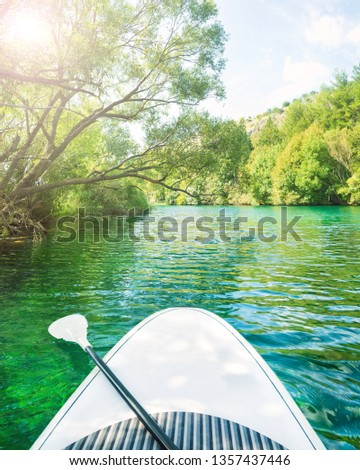 white stand up paddle board without person floating down beautiful river with clear turquoise water on sunny summer day, Zrmanja, Dalmatia, Croatia