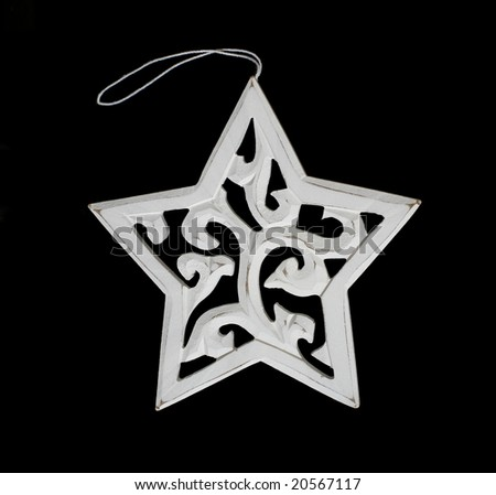 White star carved out of wood with string on black background