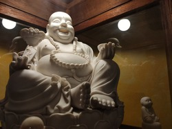 White Statue of Katyayana : smilingorlaughing and fat Buddha in the glass showcase with lighting decoration in low light background.