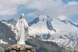 White statue of Virgin Mary, Mother of God, placed on top of the mountain. In the background there are snowy peaks of high mountains, blue sky, white clouds and a mountain lake.