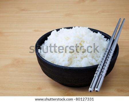 White steamed jasmine rice in black ceramic bowl with silver chopsticks