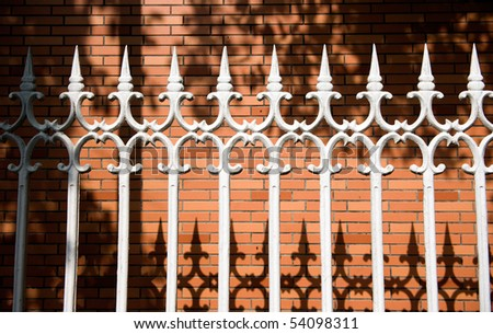 white steel picket fence in front of brick wall.