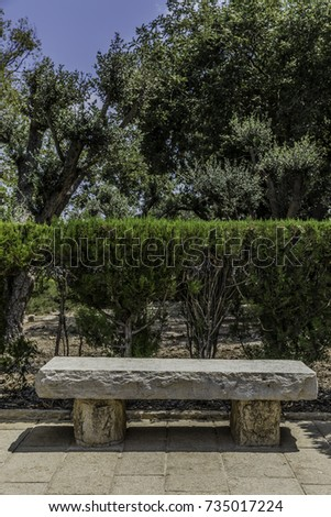 White stone bench along a footpath in the park with trimmed hedge and trees on background vertical