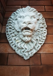 White stone lion garden fountain head with brown brick background.