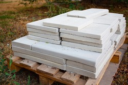 White stone paving slabs piled pile for paving the pedestrian sidewalk, closeup of building materials. Pile of tiles for sidewalks. Construction work, landscaping.