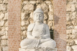 White stone statue of a Buddha in the background of masonry