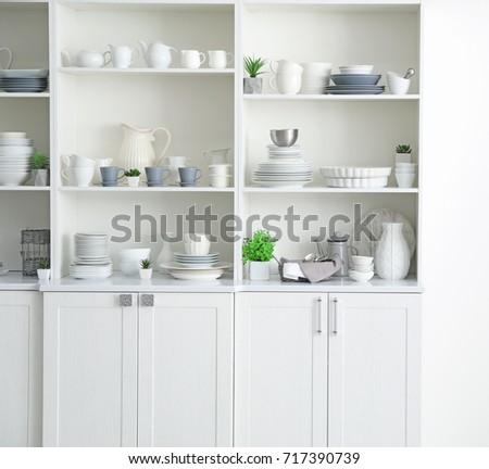 White storage stand with ceramic dishware in kitchen #717390739